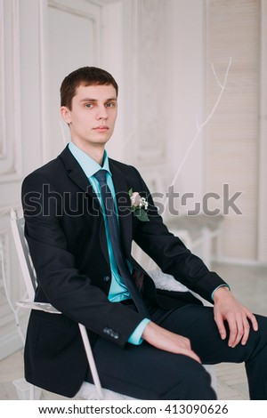 Full body portrait of young stylish businessman in tie and vest with hands on waist