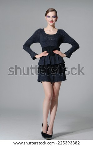 Full body Portrait of young woman in black dress posing gray background - stock photo