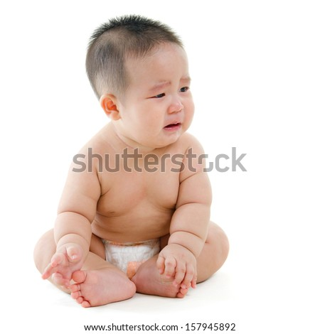 Full body sad Asian baby boy crying, sitting isolated on white background - stock photo