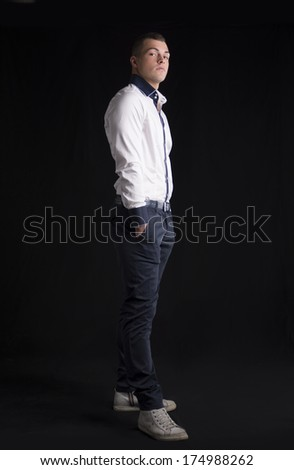 Full body shot of attractive young man with white shirt, hands in pockets, on dark background - stock photo