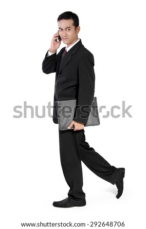 Full body shot of handsome Asian businessman walking, looking to his side while using mobile phone and holding briefcase, isolated on white background