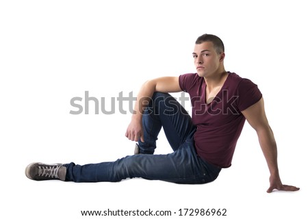 Full body shot of handsome young man with t-shirt and jeans sitting on the floor, isolated on white - stock photo