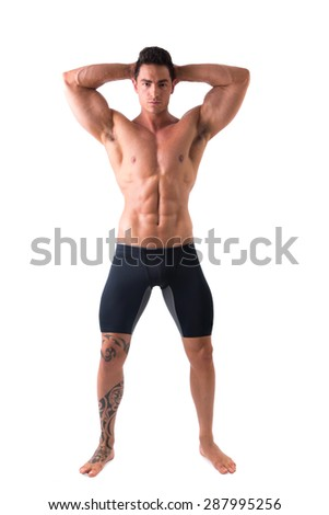 Full body shot of muscular young man standing and looking at camera smiling, shirtless, wearing tight shorts - stock photo