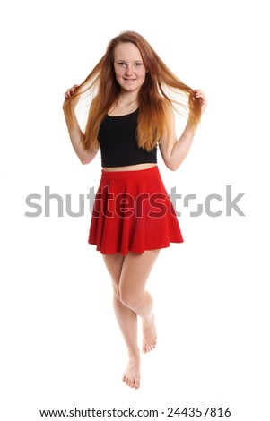 full body shot of young woman wearing red mini skirt playing with hair