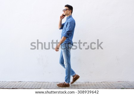 Full body side portrait of a handsome young man walking and talking on cell phone - stock photo