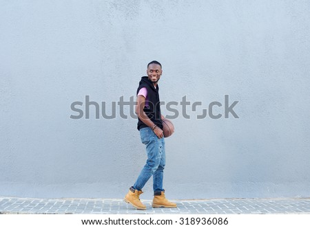 Full body side portrait of a smiling african american man walking with basketball - stock photo