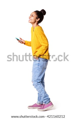 Full body side portrait of african american girl standing with cell phone on white background - stock photo