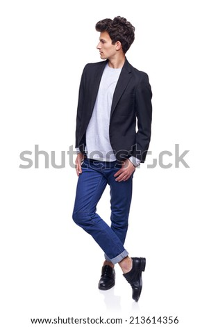 Full body side view of a fashion man with modern haircut posing standing with crossed leggs, looking away thoughtful, over white background - stock photo