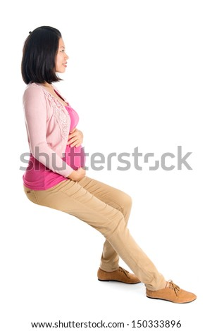 Full body six months pregnant Asian woman sitting on transparent chair, side or profile view,  isolated on white background.