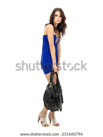 Full body slim woman in blue dress with handbag walking   - stock photo