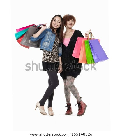 Full body two young women with shopping bags in studio - stock photo
