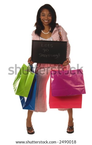 "Full body view of a Beautiful young African American girl Holding colorful shopping bags and a chalk board sign that says ""Lets Go Shopping!"""