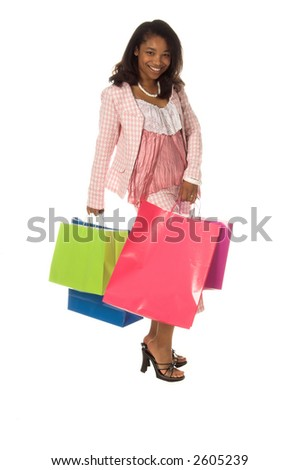 Full body view of a Beautiful young African American girl on a shopping spree and carrying an armload of colorful bags