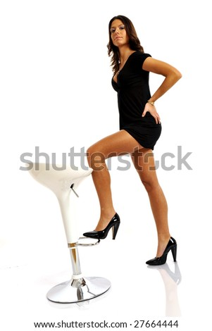 Full body view of sexy brunette with short black dress, posing with a stool. Isolated on white background. - stock photo