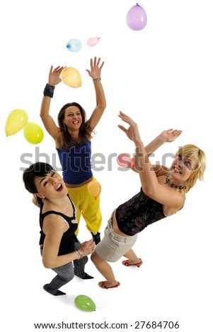 Full body view of three lovely women playing together at party with lots of colorful balloons floating all around. Isolated on white background.