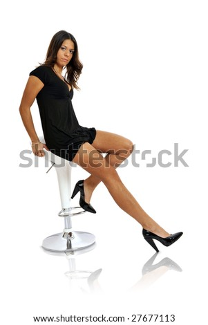 Full body view of young woman sitting on a stool in chic wear. Isolated on white background. - stock photo
