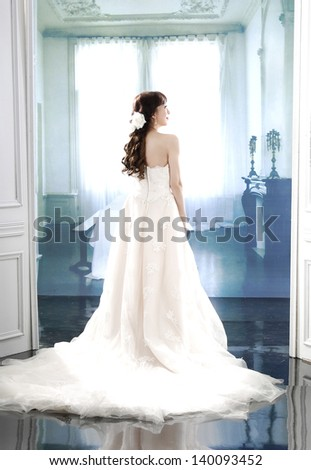 Full body young and beautiful bridge in white dress back in studio - stock photo