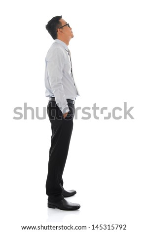 Full body young Asian businessman side view looking up. Standing isolated on white background - stock photo