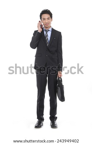 Full body young business man carrying a suitcase with mobile phone, Vertical shot. - stock photo