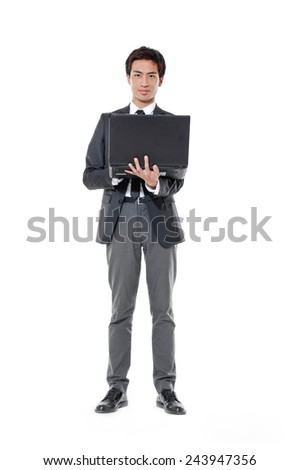 Full body young business man holding a laptop bag - stock photo
