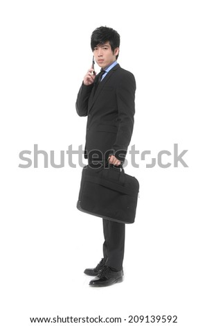Full body young business man holding a laptop bag with speaking on cellphone