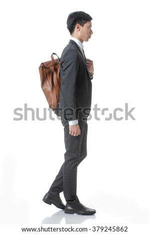 Full body young business man portrait with bag walking in studio