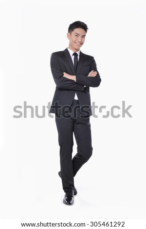 Full body young businessman with crossed arms posing in studio - stock photo