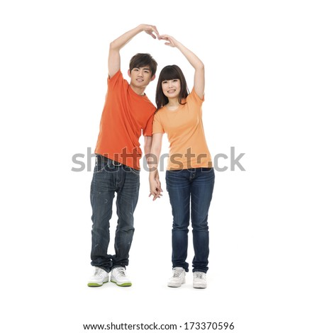 Full body young couple hands making heart shape - stock photo