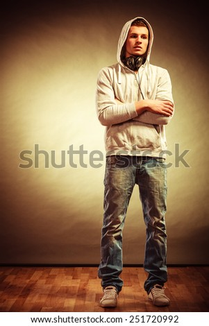 Full body young handsome man in hood with headphones listening to music grunge background