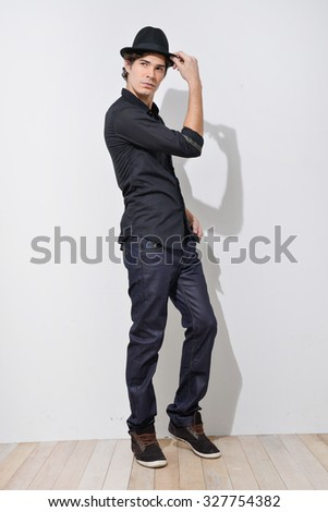 Full body Young mal model in jeans with hat posing in the studio - stock photo