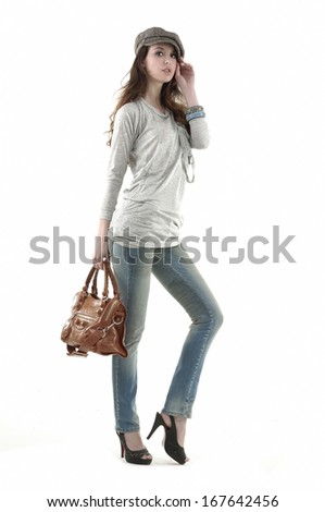Full body young stylish brunette in hat posing with bag  - stock photo