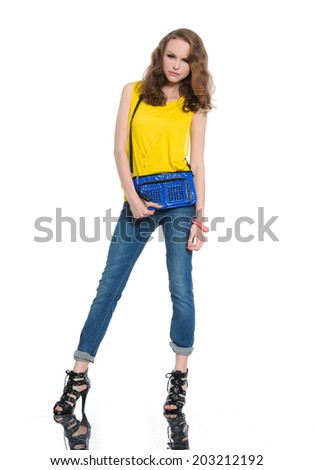 Full body young woman in shirt and blue bag posing at studio - stock photo