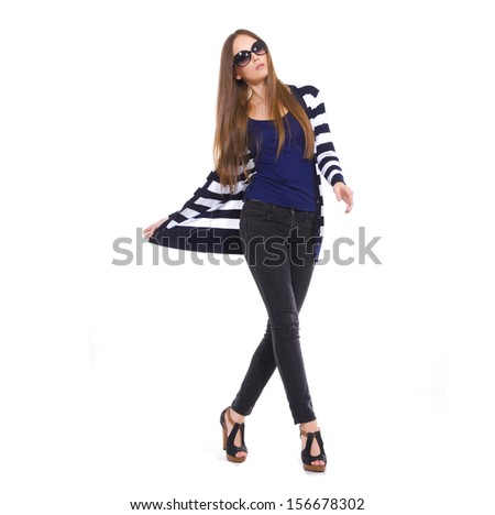 Full body young woman in sunglasses with stripy walking at studio