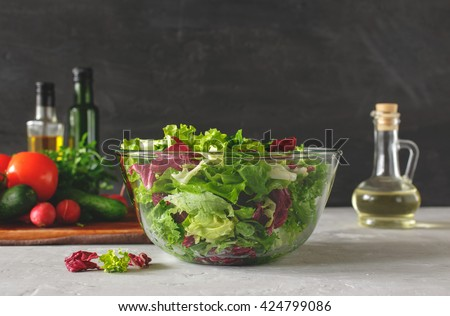 Full bowl of fresh green salad close up on a light table against a dark background on a rustic kitchen. Concept helpful and simple food - stock photo