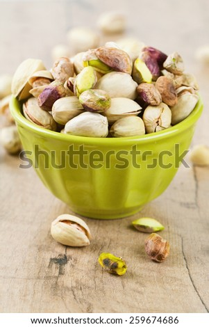full bowl of pistachio on wooden surface - stock photo