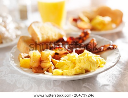 full breakfast with scrambled eggs, fried potatoes and bacon, - stock photo