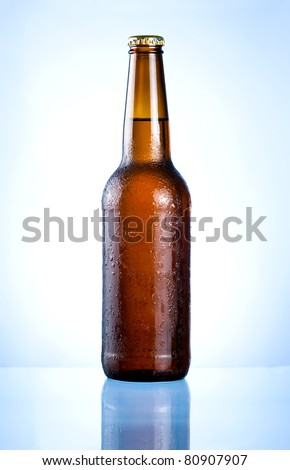 Full brown bottle with condensation on a blue background - stock photo