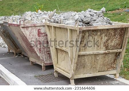 Full container of concrete debris. Trash container full of concrete debris. - stock photo