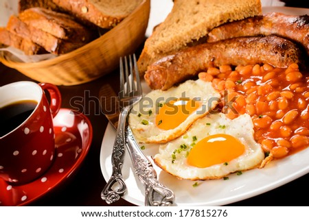 Full English breakfast in the plate.Selective focus on the front yolk egg in plate - stock photo