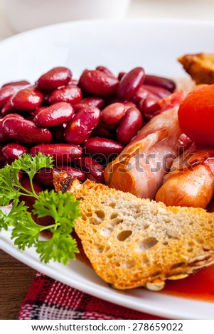Full English breakfast with bacon, sausage, fried egg and baked beans . - stock photo