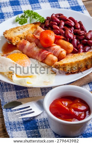 Full English breakfast with bacon, sausage, fried egg and baked beans. - stock photo