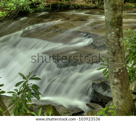 Full flowing waterfall in Spring - stock photo
