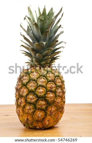 Full fresh pine-apple fruit on a wood table isolated on white background