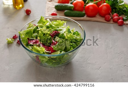 Full glass bowl of fresh green salad on a light surface. Concept helpful and simple food - stock photo