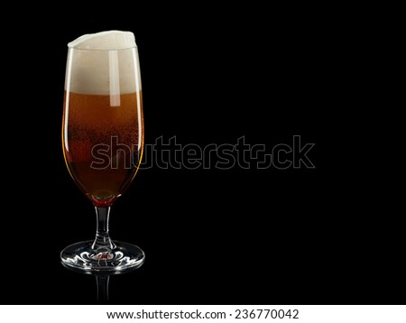 Full glass of beer with foam it is isolated on the black