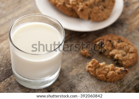 Full glass of fresh creamy milk with chocolate chip cookies on a wooden table for a tasty snack, high angle view - stock photo