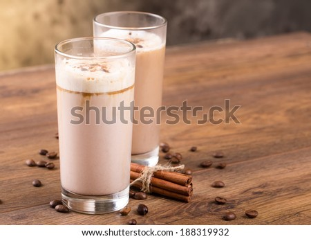 Full glass of milk cocktail and coffee beans on the wooden background