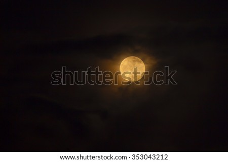 Full golden moon behind the clouds - stock photo