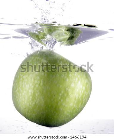 Full green apple splashing into water - stock photo
