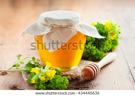 Full honey pot and honey stick with summer flowers on rustic wooden background, selective focus - stock photo